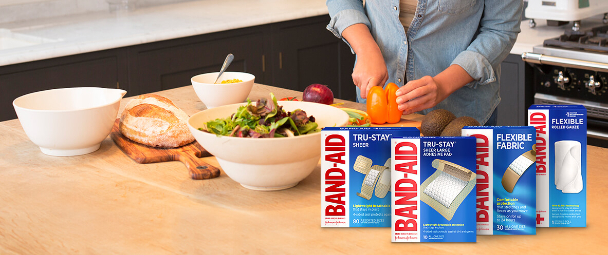 Boxes of BAND-AID® Brand TRU-STAY™ Sheer Bandages and Flexible bandages and gauze in front of a person making a salad