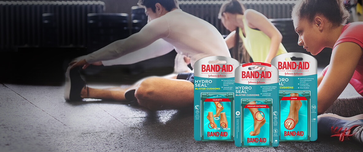Boxes of BAND-AID® Brand HYDRO SEAL® Foot Care blister cushions in front of a group of athletes stretching