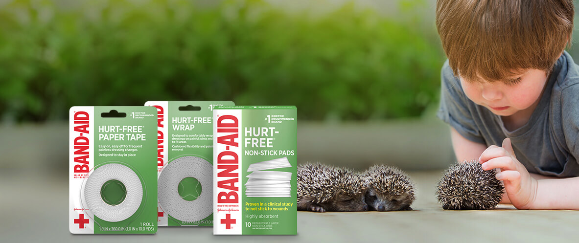Boxes of BAND-AID® Brand HURT-FREE® wound tapes and non-stick pads in front of child petting hedgehogs