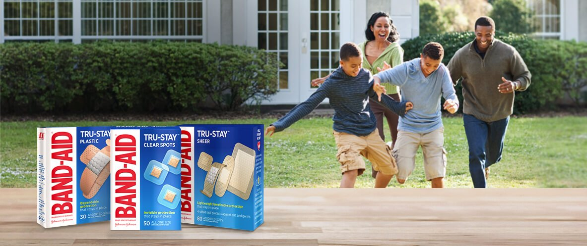 Boxes of BAND-AID® Brand TRU-STAY™ plastic, sheer and clear bandages in front of laughing family