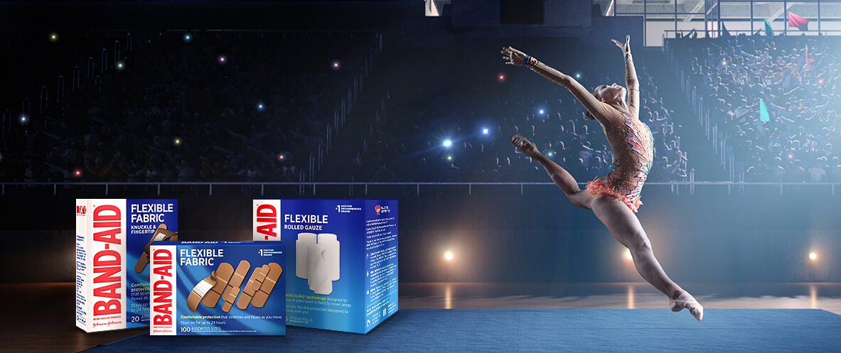 Boxes of BAND-AID® Brand FLEXIBLE bandages and gauze in front of a ballerina leaping on stage