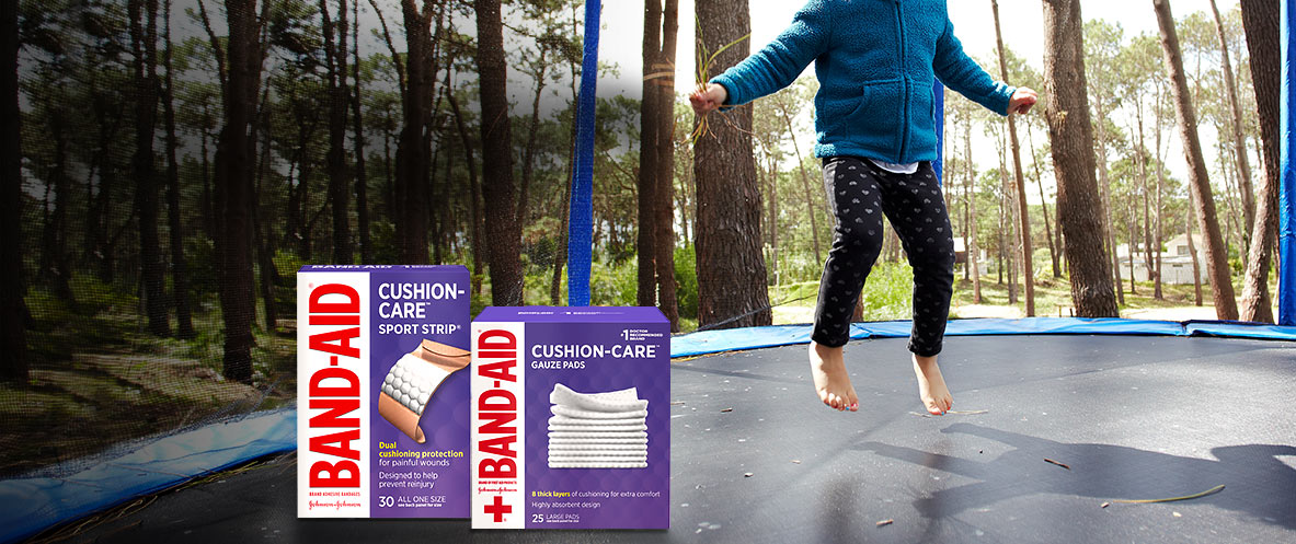 Boxes of BAND-AID® Brand CUSHION-CARE™ padded bandages and gauze pads in front of child bouncing on trampoline