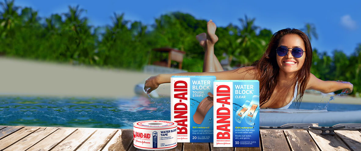 Boxes of BAND-AID® Brand WATER BLOCK® waterproof bandages, tape and shower cover in front of a woman surfing