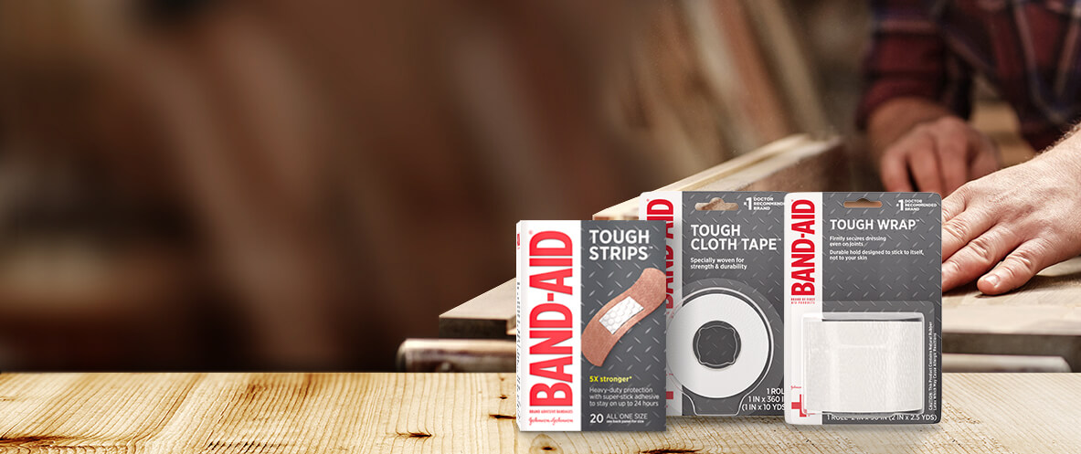Boxes of BAND-AID® Brand TOUGH heavy duty bandages, tapes and wrap in front of a carpenter cutting wood