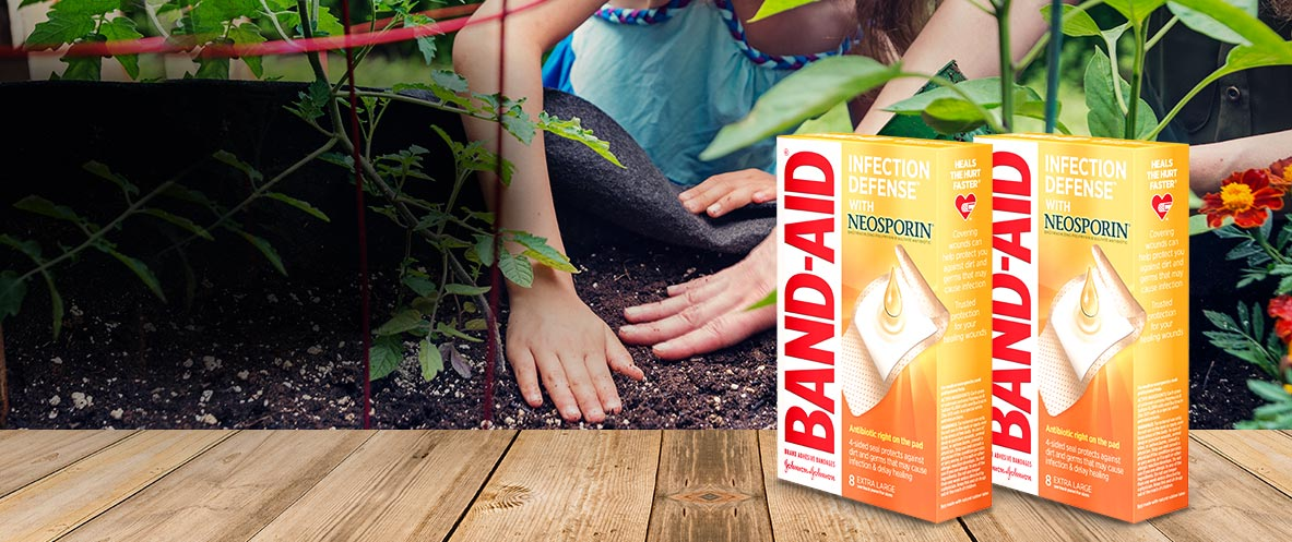 Boxes of BAND-AID® Brand INFECTION DEFENSE™ antibiotic bandages in front of a person gardening
