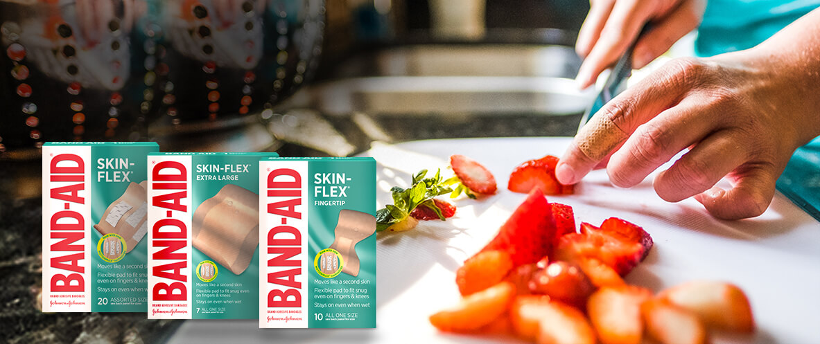 Boxes of BAND-AID® Brand SKIN-FLEX® second skin bandages in front of a person cutting strawberries wearing a finger BAND-AID®