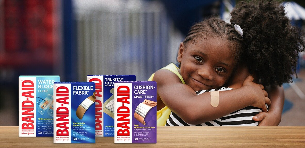 Boxes of BAND-AID® Brand products next to child wearing an adhesive bandage on her arm