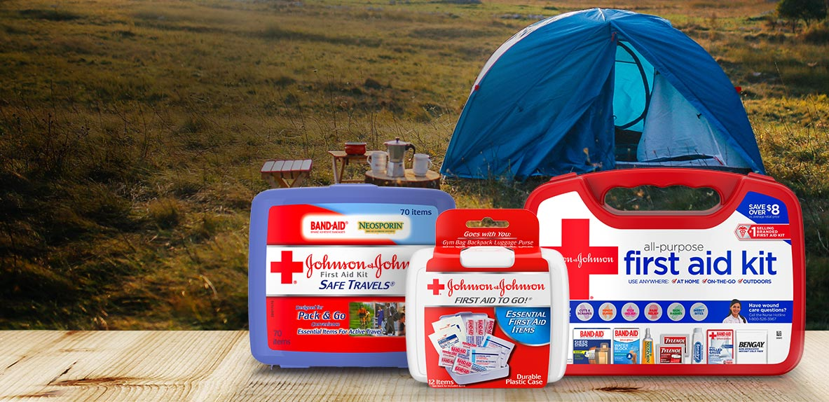 JOHNSON & JOHNSON SAFE TRAVELS® first aid kit, All-Purpose basic first aid kit and FIRST AID TO GO!® Mini First Aid Kit in front of a camping tent