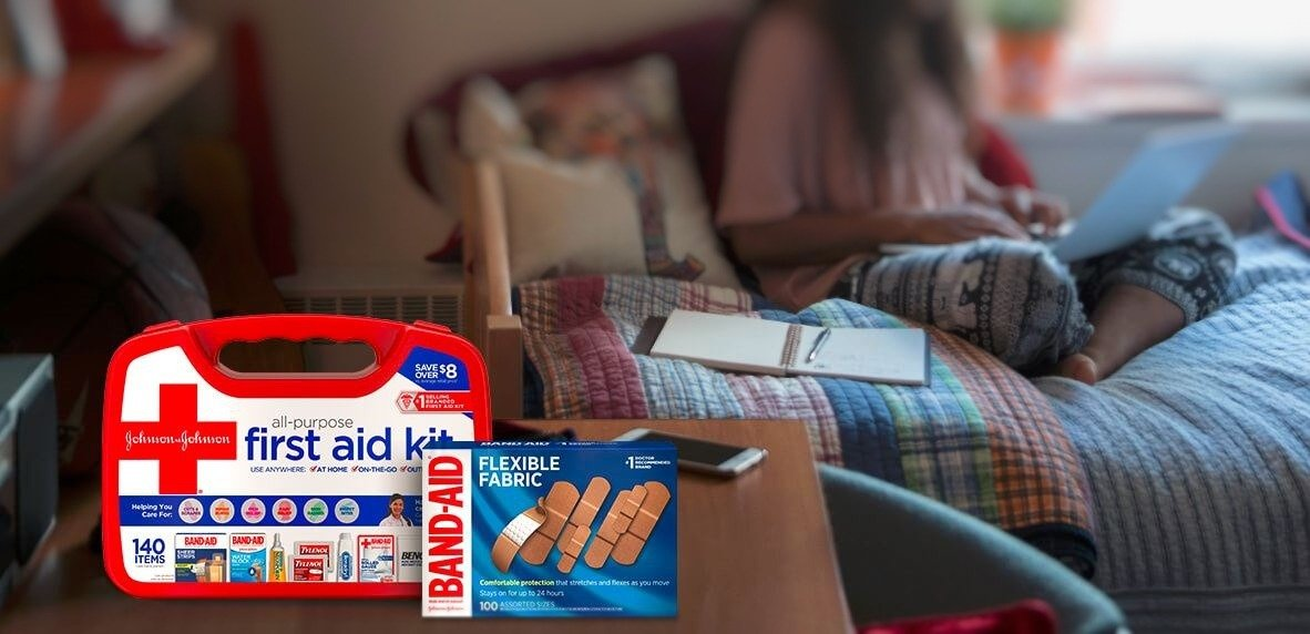 JOHNSON & JOHNSON All-Purpose basic first aid kit and BAND-AID® Brand flexible bandages next to a girl ordering products on her laptop