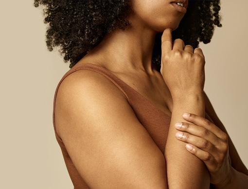 Woman holding wrist with skin toned adhesive bandage on finger